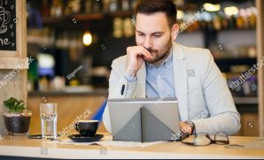 stock-photo-successful-young-businessman-using-a-tablet-while-working-in-a-modern-coffee-shop-work-anywhere-1053471215